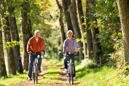 andando en bicicleta: Hombre mayor y mujer el ejercicio al aire libre con las bicicletas, son una pareja