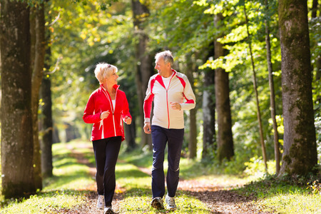 pensioners: Senior Couple doing sport outdoors, jogging on a forest road in the autumn