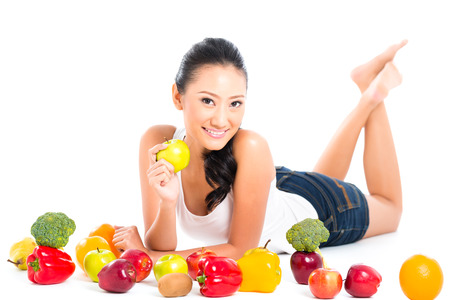 staying in shape: Asian Chinese woman eating fresh fruit