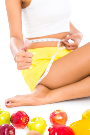 staying in shape: Young Asian woman measuring her body while having diet Stock Photo