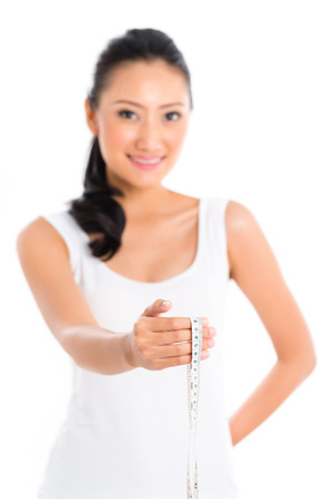 staying in shape: Asian woman measuring body