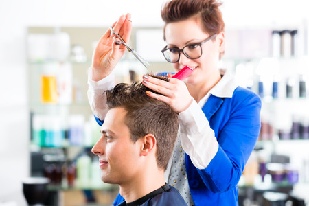 coiffeur: Female coiffeur cutting men hair in hairdresser shop