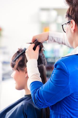 divides: Mujer coiffeur mujeres dividir el cabello en secciones con los clips en la tienda