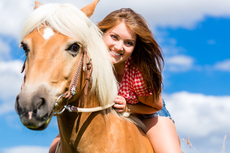 ponies: Woman riding on horse in summer meadow