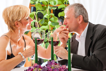 Senior couple having dinner in a restaurant, candles on the table, they are eating pasta photo