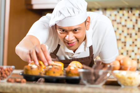 houseman: Asian man baking homemade cup cake muffins in his kitchen for dessert Stock Photo