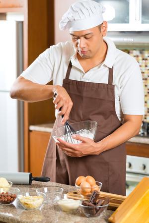 Asian man baking homemade cake in his kitchen for dessert
