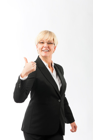 thump: Mature woman or lady with thumbs up, studio shoot