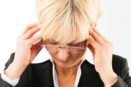 woman headache: Medicine and disease - a mature business woman with headache, burnout or migraine Stock Photo