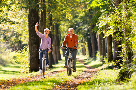 healthy path: Senior Man and woman exercising with bicycles outdoors, they are a couple Stock Photo
