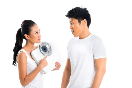 reminding: Young Asian woman reminding boyfriend of losing weight by showing scale Stock Photo