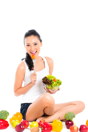 staying in shape: Asian Chinese woman eating healthy salad