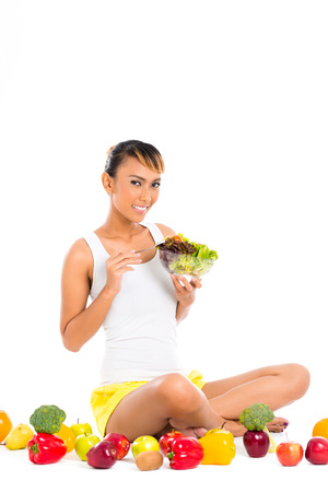 staying in shape: Asian woman eating healthy salad