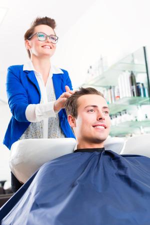 coiffeur: Female coiffeur washing men hair in hairdresser shop