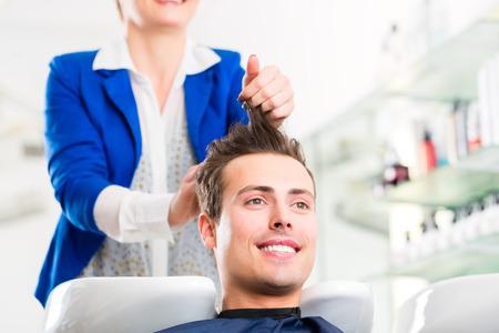 Vrouwelijke coiffeur wassen mannen haar in kapper winkel