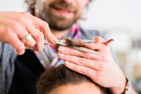 Barber trimming man hair in haircutter shop photo