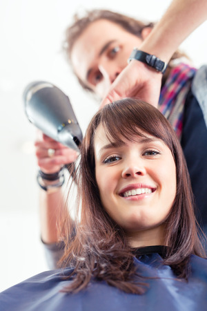 blow dry: Hairdresser blow dry woman hair in shop Stock Photo