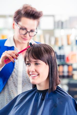 coiffeur: Female coiffeur cutting women hair in hairdresser shop