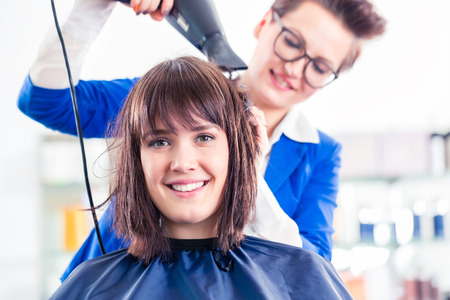 blow dry: Female coiffeur blow dry women hair with blow dryer in shop