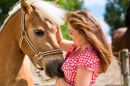 petting: Woman petting horse on pony farm