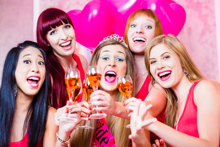 bachelor: Bride and friends celebrating hen night with champagne in club