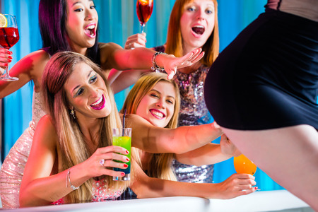 striptease women: Friends watching striptease in strip club grabbing at female stripper