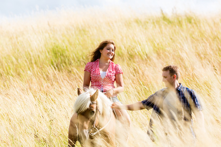 Couple leading horse thru summer meadow photo
