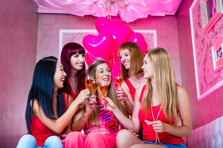 Bride and friends celebrating hen night with champagne in club