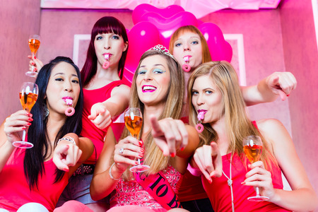 Bride and friends celebrating hen night with champagne and whistles in club