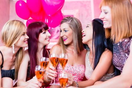 jovenes tomando alcohol: Mujeres de fiesta con champ�n en club nocturno Foto de archivo