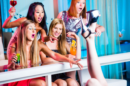 Friends watching striptease in strip club grabbing at female stripper