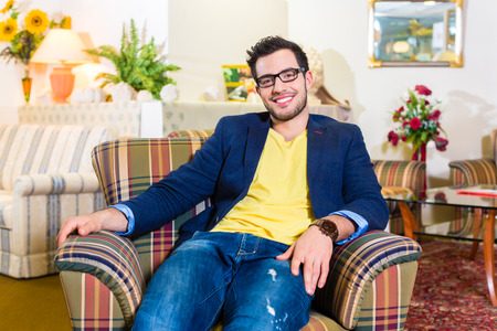 specialised: Young man testing and buying armchair in furniture store Stock Photo