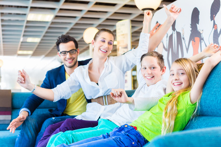 specialised: Family selecting together sofa in home-centre to furniture store