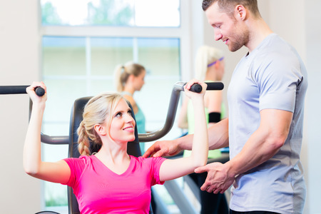 personal trainer woman: Woman with personal trainer doing sport in gym Stock Photo