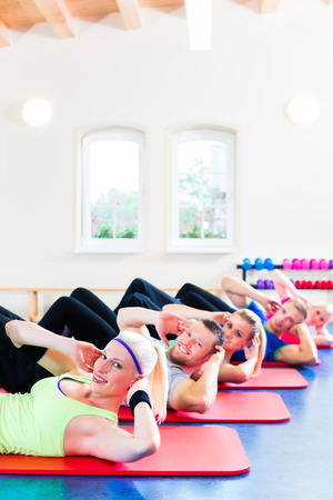 crunches: fitness people in gym doing crunches
