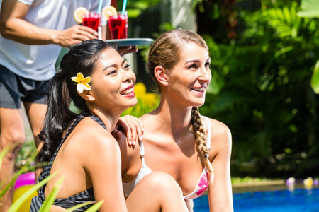 bikini pool: Two girls or women in vacation, Asian and Caucasian, in tropical garden at hotel pool tanning being served drinks or cocktails Stock Photo