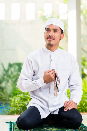house of prayer: Asian Muslim man praying at home sitting on prayer carpet in his house in front of the tropical garden