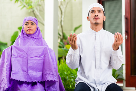woman praying: Asian Muslim couple, man and woman, praying at home sitting on prayer carpet in their house in front of the tropical garden Stock Photo