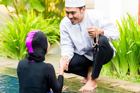 observant: Muslim woman or girl in swimming pool in tropical garden wearing Burkini halal swimwear greeting her husband