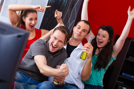 telly: Two couples watching sports in the telly, they all are really excited, drink beer and cheer their team