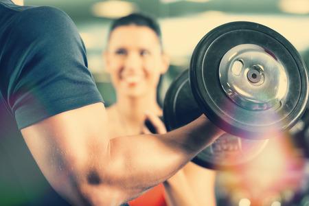フィットネス: 男またはダンベル、クローズ アップとスポーツを行使ジムで彼の個人的なフィットネス トレーナーとボディービルダー