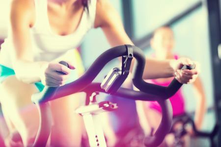 vrouwen: Young People - groep vrouwen en mannen - doen sport spinnen in de sportschool voor fitness