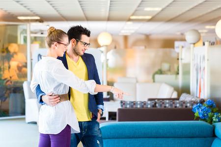 Giovane coppia scegliendo insieme divano in negozio di mobili per arredare casa