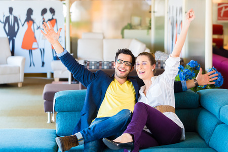 furniture store: Young couple selecting together sofa in furniture store to furnish home