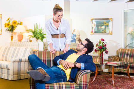Young couple selecting together armchair in furniture store Stock Photo