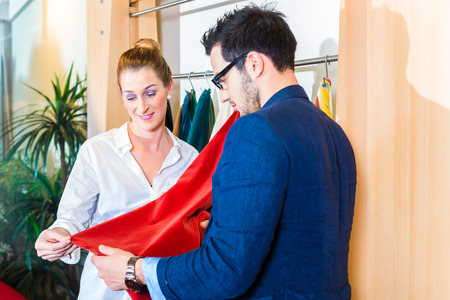Young couple selecting seat cover for sofa in furniture store