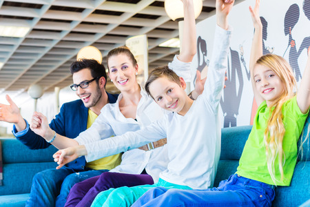 furnish: Family selecting together sofa in home-centre to furniture store