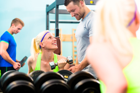 dumb bells: Woman in gym training with dumb bells