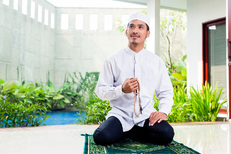 praying: Asian Muslim man praying at home sitting on prayer carpet in his house in front of the tropical garden