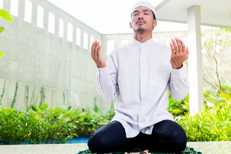 plea: Asian Muslim man praying at home sitting on prayer carpet in his house in front of the tropical garden
